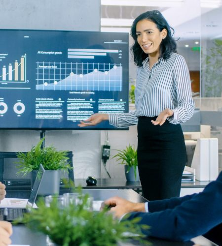 Beautiful Businesswoman Gives Report/ Presentation to Her Business Colleagues in the Conference Room, She Shows Graphics, Pie Charts and Company's Growth on the Wall TV.