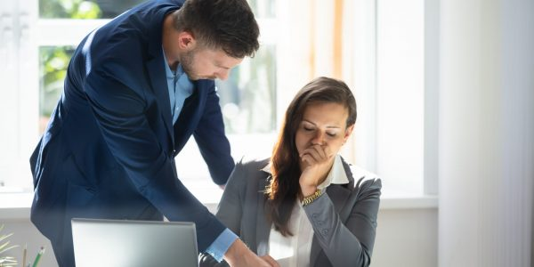 Young Businessman Explaining Graph To Sad Female Employee At Workplace